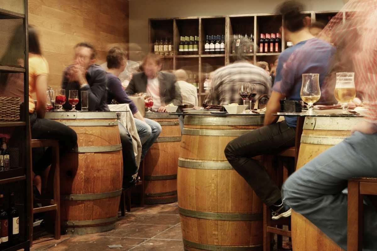 Fotografía del interior de un bar rústico, taberna típica de Madrid, con mesas de barriles de vino
